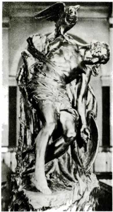 Умирающий Кухулин. Он привязан к каменному столбу, роняет меч, на плече у него богиня войны в образе ворона. Современная скульптура в Дублине.